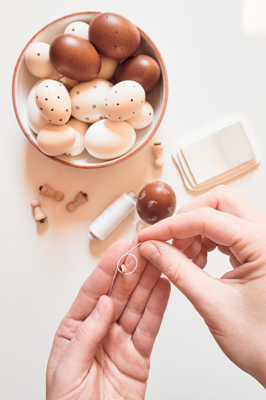 Osterei bestempeln - Aufhängung basteln mit Streichholz und Faden