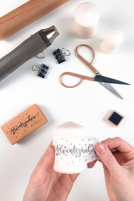 Seidenpapier mit Stempelmotiv auf einer Stumpenkerze positionieren