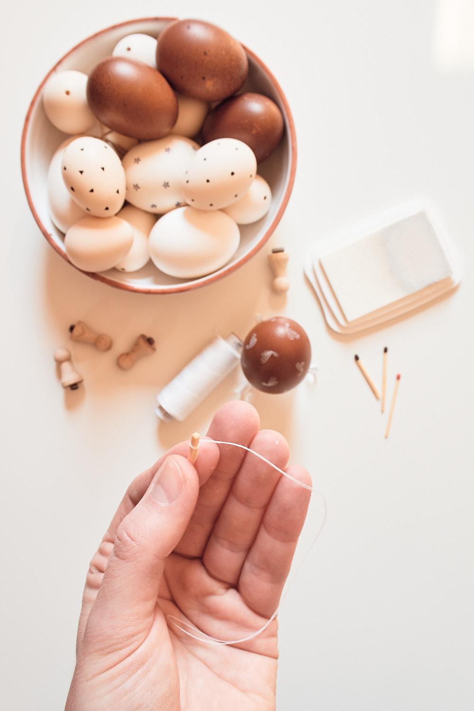 Osterei bestempeln - Aufhänung basteln mit Streichholz und Faden